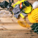 Protective hard hat, headphones, gloves and glasses on wooden background, copy space, top view